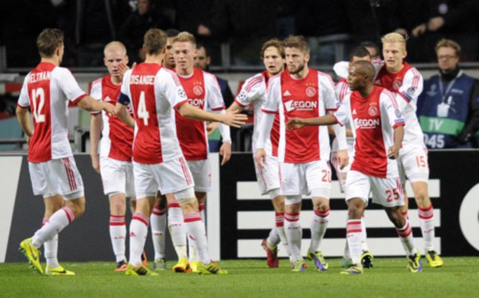 FILE: Ajax Amsterdam's Thulani Serero celebrates scoring a goal with teammates during the UEFA Champions League group H football match between Ajax Amsterdam and FC Barcelona at the Amsterdam Arena in Amsterdam on 26 November, 2013. Picture: AFP.