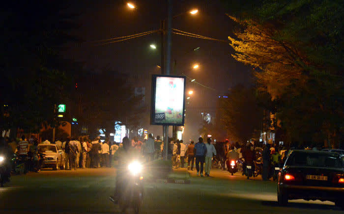 """People gather on Kwame Nkruma Avenue near Hotel Splendid where the attackers remain with sporadic gunfire continuing in Burkina Faso's capital Ouagadougou on 15 January 2016. Attackers have killed """"several people"""" at a restaurant opposite a four-star hotel where the assailants are holed up. Picture: AFP."""