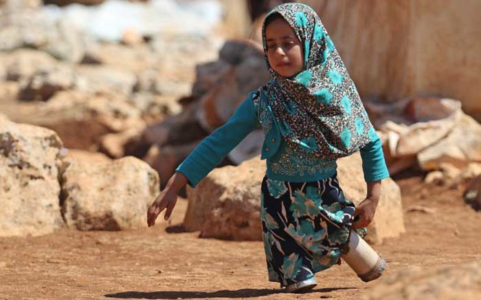 In this file photo taken on 20 June 2018 eight-year-old Maya Mohammad Ali Merhi walks using prosthetic legs made by her father from tin cans in a camp for displaced people, in the northern Syrian province of Idlib. Picture: AFP.