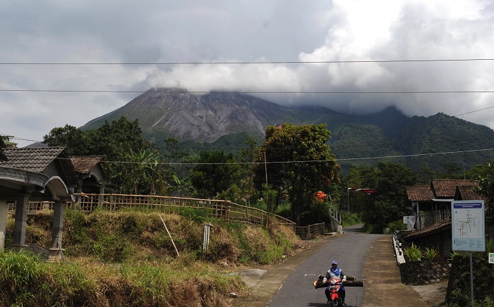 A villager rides his motorcycles along a village road as smoke spew from Mount Merapi in Yogyakarta on November 27, 2020, after the Indonesia Geological agency raised the status alert for Merapi to the second-highest ahead of a possible eruption. Picture: AFP