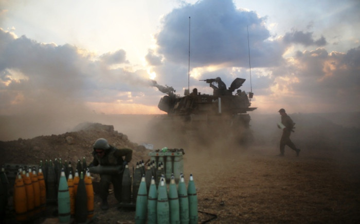FILE: Israeli soldiers fire towards the Gaza Strip from their position near Israel's border with the coastal Palestinian enclave on 19 July 2014. Picture: AFP.