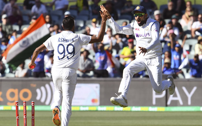 India's Virat Kohli (R) and Ravi Ashwin celebrate an attempted run-out of Australia's Steve Smith during the second day of the first cricket Test match between Australia and India played in Adelaide on 18 December 2020. Picture: AFP