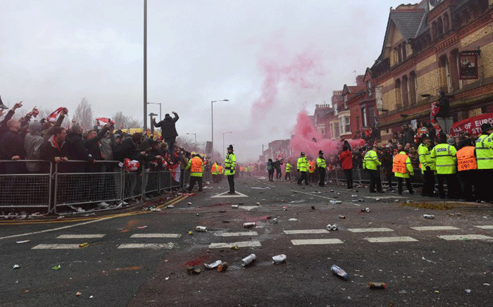 Police control supporters through smoke and beercans before the UEFA Champions League first leg quarter-final football match between Liverpool and Manchester City, at Anfield stadium in Liverpool, north west England on 4 April, 2018. Picture: AFP.
