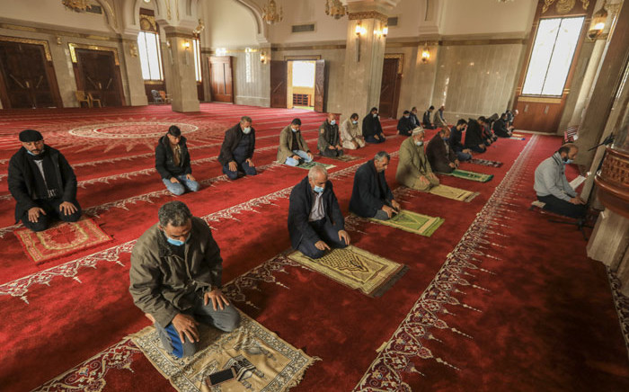 Palestinians wearing masks pray while maintaining social distancing as a preventative measure against the COVID-19, in a mosque that reopened after the easing of restrictions, in Gaza City on 10 January 2021. Picture: Mahmud Hams/AFP