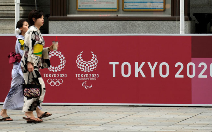 FILE: Pedestrians walk in front of a board displaying the Tokyo 2020 logos for the upcoming Tokyo 2020 Olympic Games on 23 July 2019, nearly one year before the start of the Tokyo 2020 Olympic Games. Picture: AFP