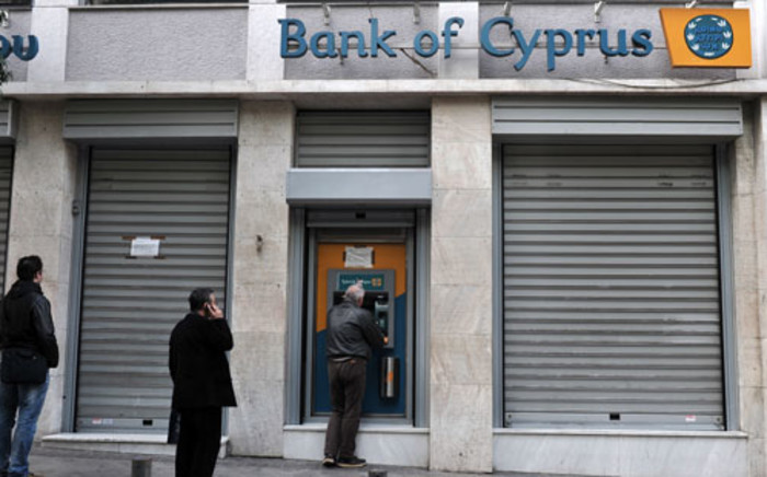 "People queue to withdraw money from a Bank of Cyprus branch' ATM in Athens on March 19, 2013 while Cypriot banks remain closed in Greece until March 21. Athens was ""ready"" to absorb the subsidiaries of three Cyprus banks active in Greece, the Greek finance minister said as the eurozone sought to amend a controversial levy on the island nation's bank deposits. Picture: AFP."