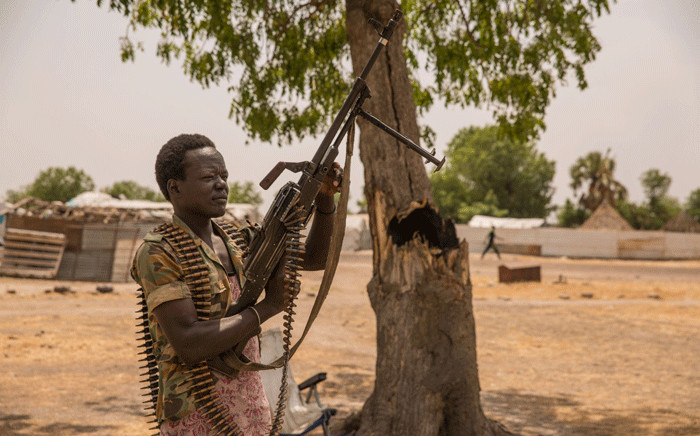 FILE: A government soldier poses with a gun on 7 March 2017 in Leer, where famine has been declared since February 2017. Picture: AFP.