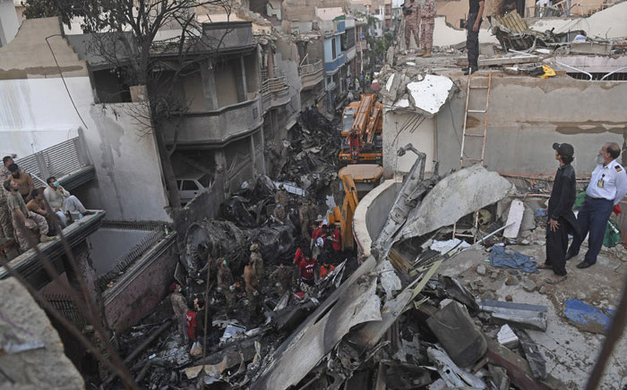 Security personnel search for victims in the wreckage of a Pakistan International Airlines aircraft after it crashed in a residential area in Karachi on 22 May 2020. Picture: AFP