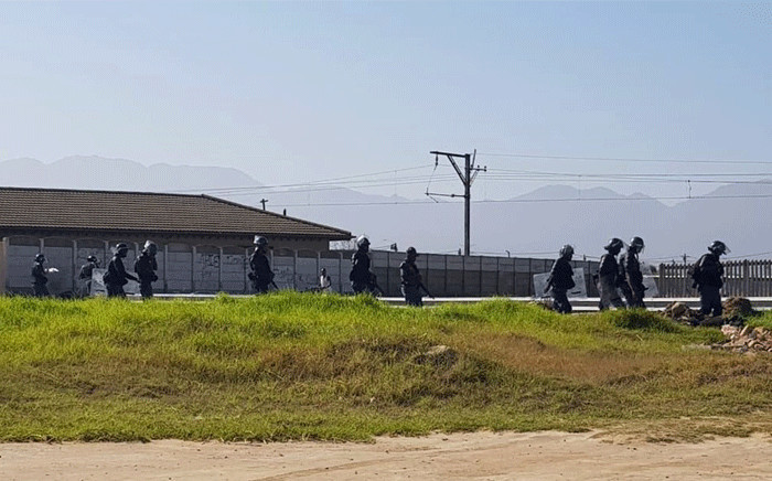 Police on the scene of a land invasion in Somerset West. Picture: @senkamin/Twitter