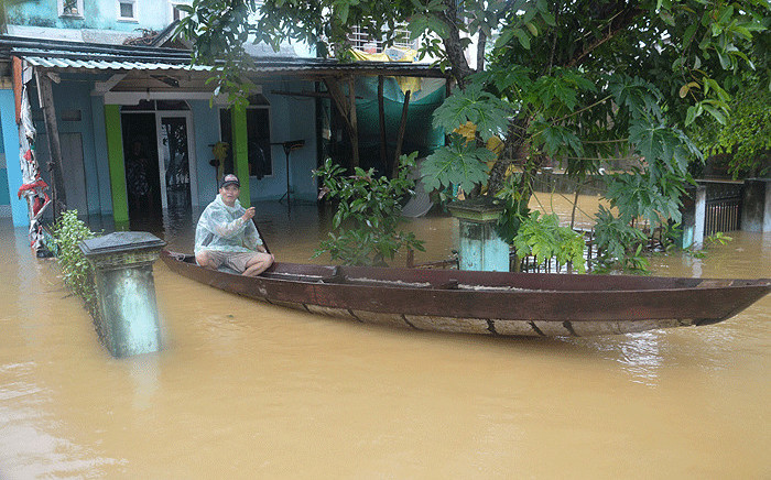 In this picture taken on 5 November 2017 a man sits on a boat in front of his flooded home in Hoa Vang district, central city of Danang following the passage of the typhoon Damrey on central Vietnam. Picture: AFP.