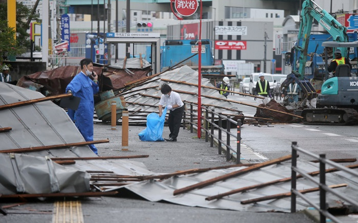 A clean-up crew works to remove roofs which were blown off into a street by strong winds brought by Typhoon Haishen in Fukuoka as the storm passes the southern Japanese island of Kyushu on 7 September 2020. Picture: AFP.