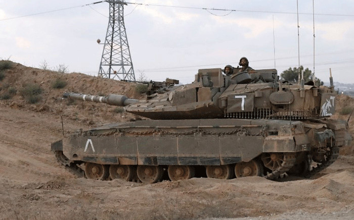 Israeli soldiers ride in the turret of a Merkava battle tank near the Kibbutz of Nahal Oz, along the border with the Gaza Strip on 20 July, 2018. Picture: AFP.