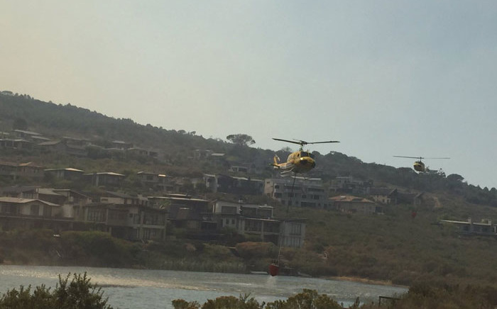Helicopters collect water from the Boskloof Estate dam to fight a vegetation fire in Somerset West. Picture: Natalie Malgas/EWN