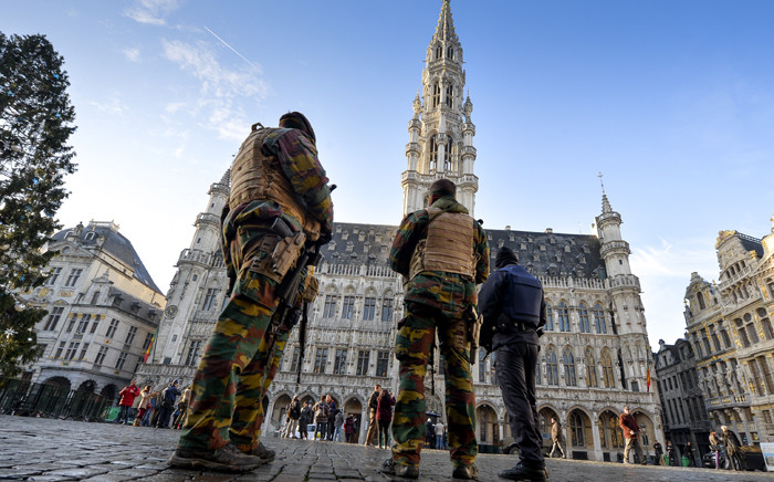 Soldiers and police patrol on Brussels' Grand Place as the Belgian capital remains on the highest possible alert level on November 23, 2015. Belgian police arrested five more people in a new series of anti-terrorism raids Monday, prosecutors said, as the capital Brussels was locked down for a third day under a state of maximum alert. Picture: AFP.