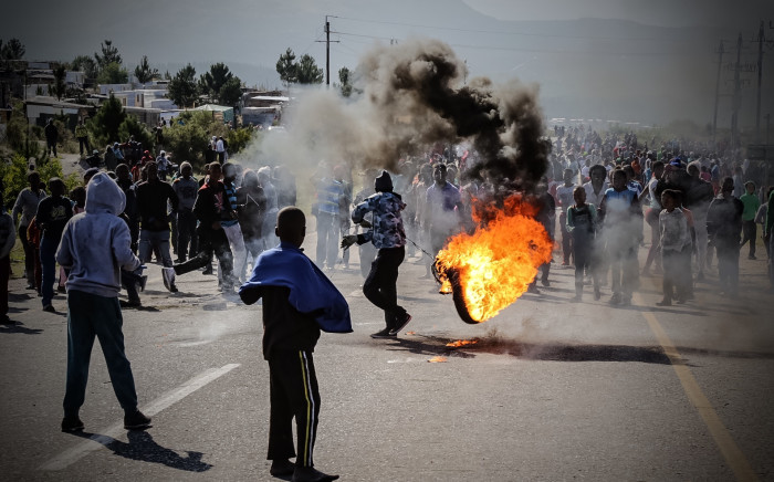 FILE: A protester swings around a burning tyre. Picture: Thomas Holder/EWN.