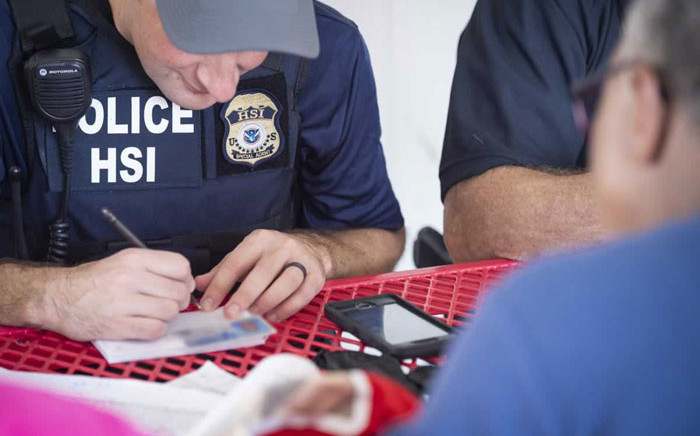 FILE: This image released by the US Immigration and Customs Enforcement (ICE) shows a Homeland Security Investigations (HSI) officer checking an identity document on 7 August 2019. Picture: AFP