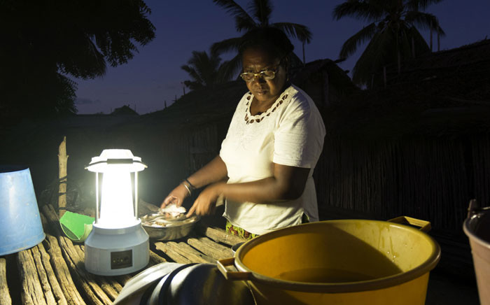 FILE: Yollande Randrianambinina, 53, cooks in front of her house in the village of Ambakivao, Madagascar, on 23 April 2018. Randrianambinina is a member of a group of four women who have become their community's first solar engineers. Picture: AFP