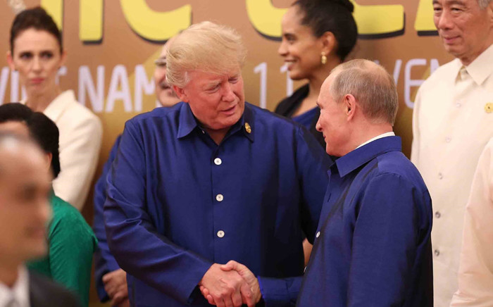 President Donald Trump shakes hands with Russia's President Vladimir Putin as they pose for a group photo ahead of the Asia-Pacific Economic Cooperation Summit leaders gala dinner in the central Vietnamese city of Danang on 10 November 2017. Picture: AFP.