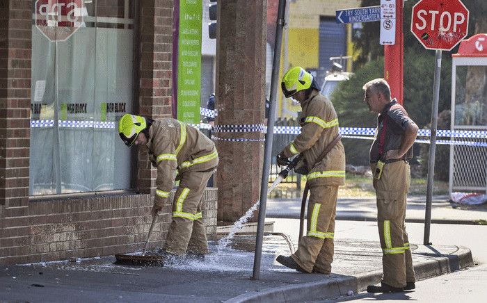 Firemen wash away bloodstains after a security guard was shot dead with another man fighting for his life after a drive-by shooting outside a popular Melbourne nightclub on 14 April, 2019. Picture: AFP.