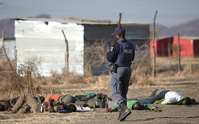 Police stand over the dead bodies of victims shot during a stand off on Thursday, 16 August, 2012. Picture: Taurai Maduna/Eyewitness News.