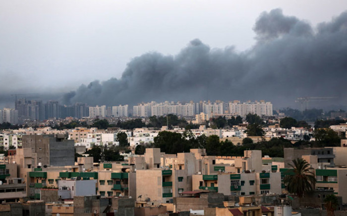 FILE: Smoke fills the sky over Tripoli after fighting between rival militias in August 2014. The groups have been fighting since mid-July in the capital for control of the city's main airport. Picture: EPA.