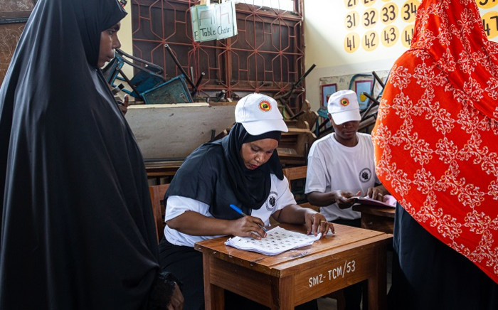 A Tanzanian electoral official checks the voter's roll at a polling station in the outskirts of Stone Town, Zanzibar, on 28 October 2020. Picture: AFP
