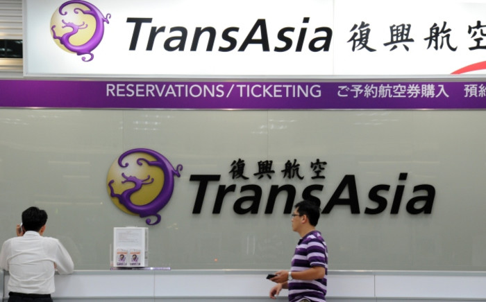 Local journalists wait in front of a TransAsia reservations desk at the Sungshan airport in Taipei on 23 July 2014. More than 40 people were killed when flight GE222 crashed near Magong airport on the outlying Penghu island in Taiwan after having requested a second attempt to land. Picture: AFP.