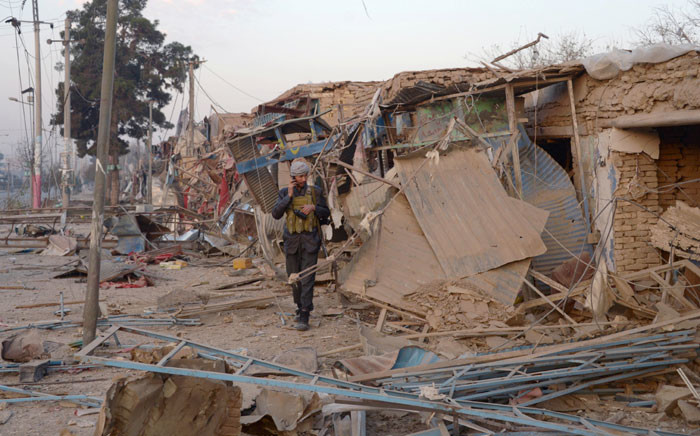 An Afghan security personnel walks along damaged buildings as he inspects the site of a bomb attack targeting the German consulate in Mazar-i-Sharif on 11 November 2016. Picture: AFP