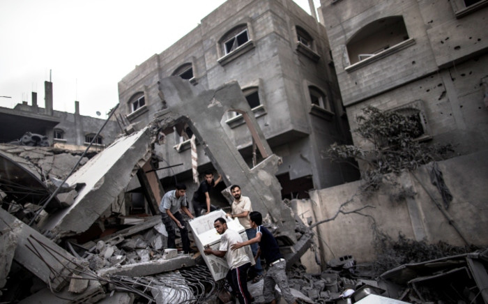 Palestinian men recover items from the rubble of a building following an Israeli military strike in the Jabalia district in the northern Gaza Strip, on 24 July 2014. Picture: AFP.