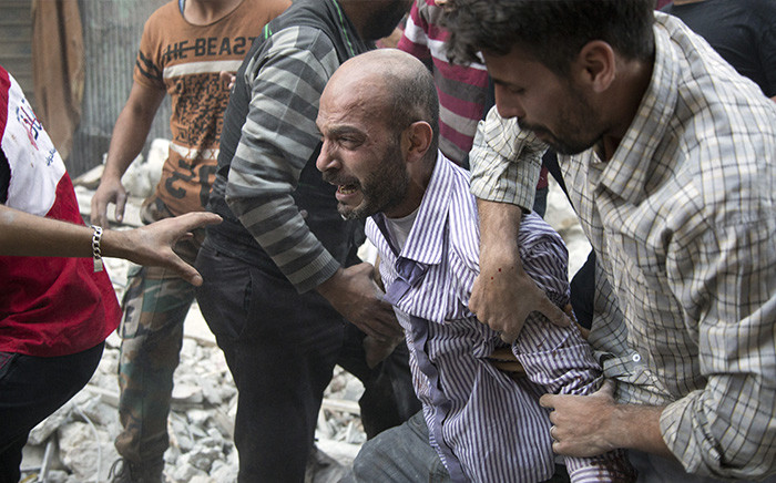 A grief-striken Syrian man is comforted by people as rescuers pull the body of his daughter from the rubble of a building. Picture: AFP.