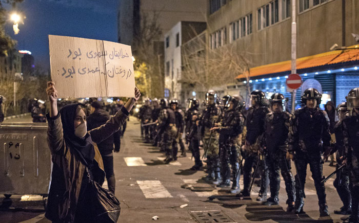 An Iranian woman holds a placard reading in Farsi: 'Your mistake was unintentional, your lie was intentional' during a demonstration outside Tehran's Amir Kabir University on 11 January 2020. Picture: AFP