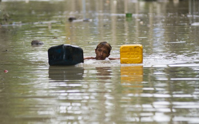 A flood-affected resident swims through floodwaters in Kalay, upper Myanmars Sagaing region on August 3, 2015. Relentless monsoon rains have triggered flash floods and landslides, destroying thousands of houses, farmland, bridges and roads with fast-flowing waters hampering relief efforts. Picture: AFP.