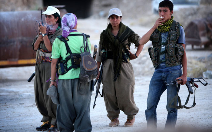Female members of the Kurdistan Workers' Party (PKK) and an Iraqi Kurdish Peshmerga fighter take positions on the front line in Makhmur, some 50 km south of Arbil, the capital of the autonomous Kurdish region of northern Iraq. Picture: AFP