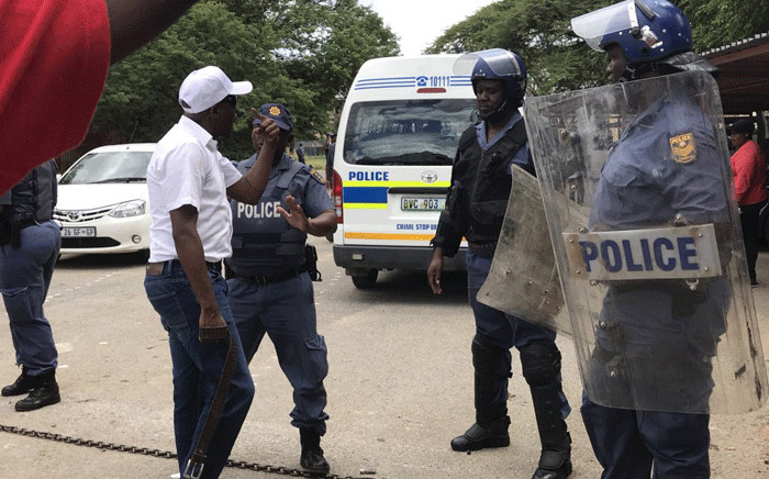A demonstrator seen with police in the North West after Nehawu clashed with ANCYL members over calls for Premier Supra Mahumapelo to step down. Picture: Masechaba Sefularo/EWN