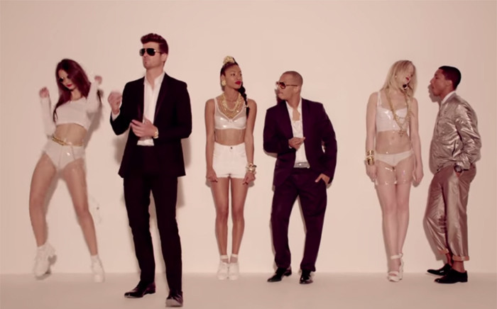 "A screen grab from Robin Thicke's music video, ""Blurred Lines"", featuring T.I and Pharrell."