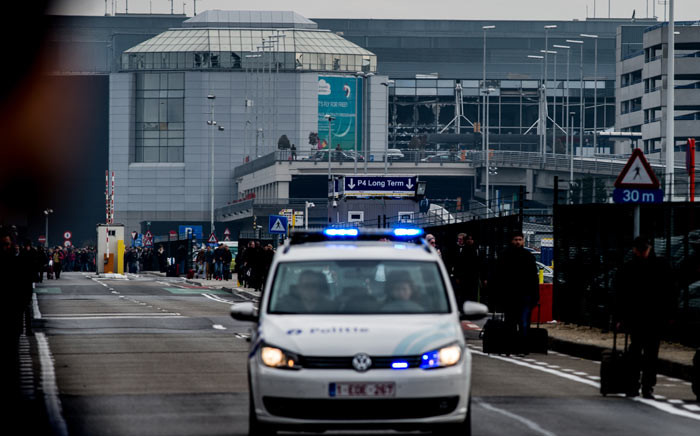 A Belgian police vehicle drives past passengers who are evacuating the Brussels Airport of Zaventem after at least 13 people were killed and 35 injured as twin blasts rocked the main terminal on 22 march 2016. Picture: AFP.