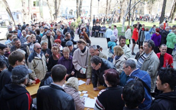 People queue to get their Russian passports in the Crimean capital of Simferopol on 24 March. Picture:AFP.