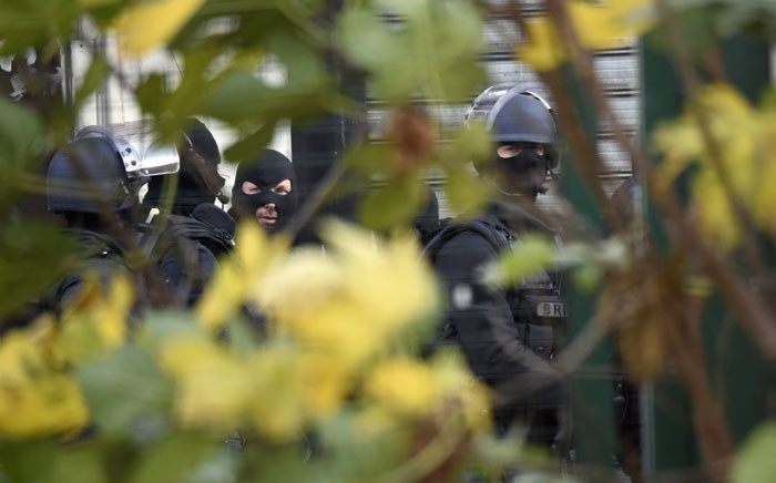 Members of the BRI, a special intervention unit of the French police, are pictured in combat position in the northern Paris suburb of Saint-Denis city centre, on 18 November 2015, as French Police special forces raid an appartment, hunting those behind the Paris attacks on 13 November. Picture: AFP.