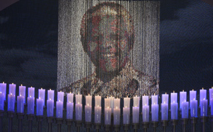 Candles are lit under a portrait of Neslon Mandela before the funeral ceremony of South African former president Nelson Mandela in Qunu on December 15, 2013. Picture: AFP