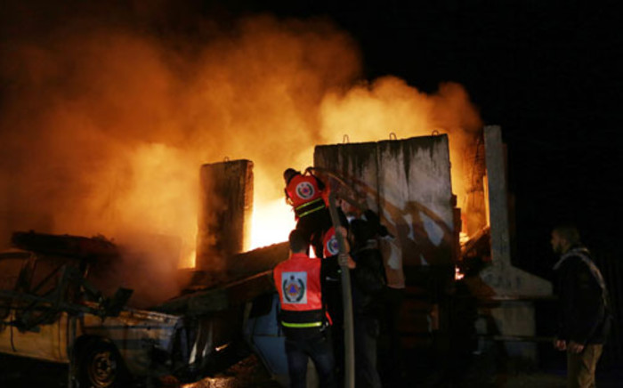Palestinians extinguish a fire after Israeli air strikes targeted an electricity generator that fed the house of Hamas's Prime Minister Ismail Haniyeh in Gaza City, on November 15, 2012. Picture: AFP.