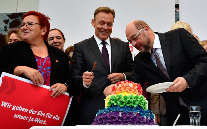 Thomas Oppermann (centre), parliamentary group leader of the social democratic SPD party, and SPD leader and candidate for chancellor Martin Schulz (right) cut a wedding cake in rainbow colors and decorated with figurines of two women and two men at the Bundestag in Berlin on 30 June 2017. The German parliament legalised same-sex marriage, days after Chancellor Angela Merkel said she would allow her conservative lawmakers to follow their conscience in the vote. Picture: AFP.