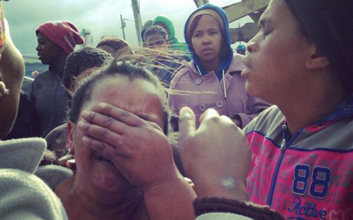 A woman weeps after her shack was destroyed by fire as police carried out mass evictions in Nomzamo near Strand in Cape Town on 3 June 2014. Picture: Carmel Loggenberg/EWN.