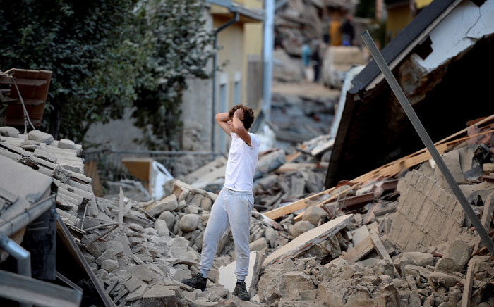 A man stands among damaged buildings after a strong earthquake hit central Italy, in Amatrice on August 24, 2016. Picture: AFP
