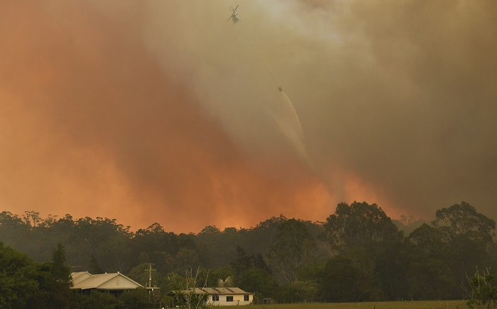 A helicopter drops water on a homestead as bushfires impact on farmland near the small town of Nana Glen, some 600kms north of Sydney on 12 November 2019. Picture: AFP