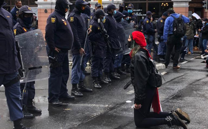 A protester kneels in front of police during an anti-gender-based violence protest in front of Parliament in Cape Town on 29 August 2020. Picture: Courtney Savage