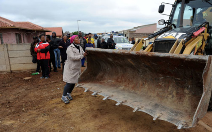 A woman tries to stop a bulldozer from demolishing a house in Lenasia's Extension 13 in southern Johannesburg, on 9 November 2012. Picture: Werner Beukes/SAPA