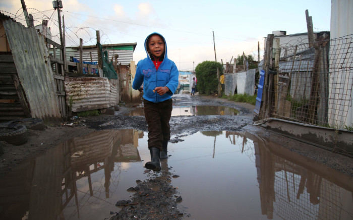 Wearing his waterproof boots, a boy from Khayelitsha does not mind the puddles. Picture: Bertram Malgas/EWN.