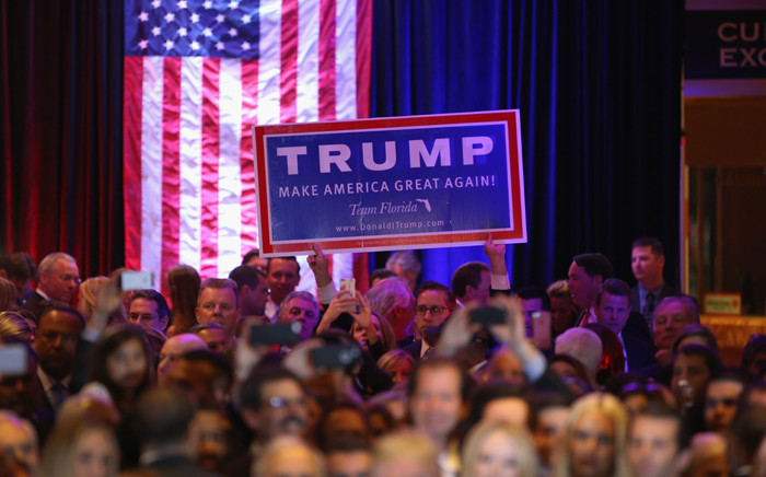 FILE: A supporter holds a sign as Republican presidential candidate Donald Trump speaks after winning the New York state primary on 19 April, 2016 in New York City. Picture: AFP.