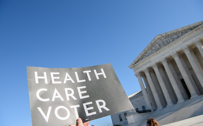 FILE: A demonstrator holds a sign in front of the US Supreme Court in Washington, DC, on 10 November 2020 as the high court opened arguments in the long-brewing case over the constitutionality of the 2010 Affordable Care Act. Picture: AFP.