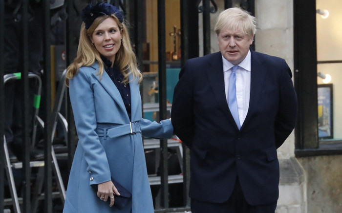 FILE: Britain's Prime Minister Boris Johnson with his partner Carrie Symonds leave after attending the annual Commonwealth Service at Westminster Abbey in London on 9 March 2020. Picture: Tolga AKMEN/AFP